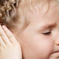девочка указывает на больное ухо