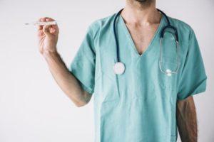 врач держит градусник