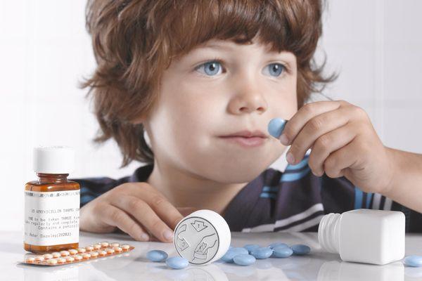 ребенок держит таблетку